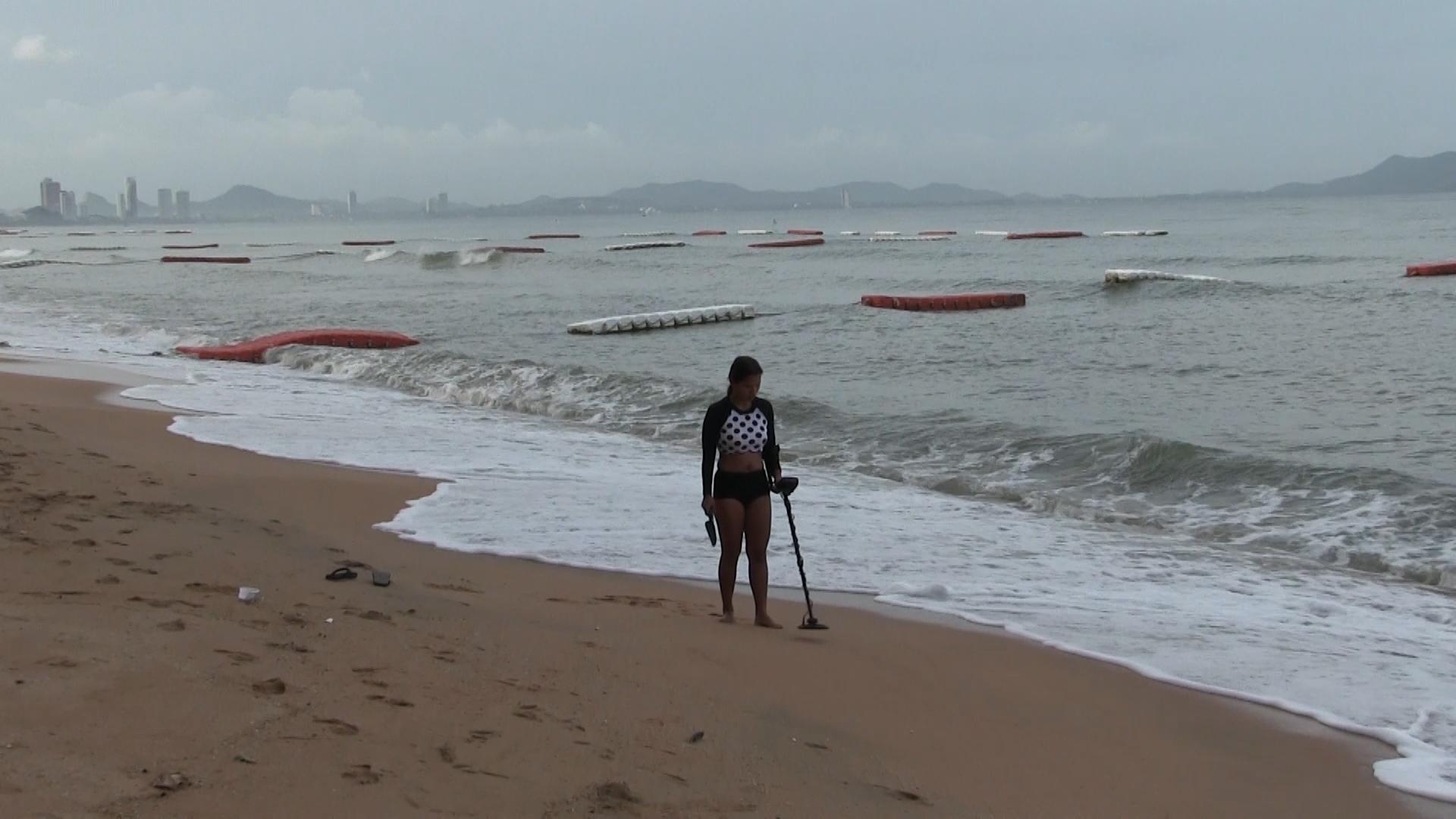 Поиск с металлоискателем на пляже в прибойной зоне. Тиаланд.